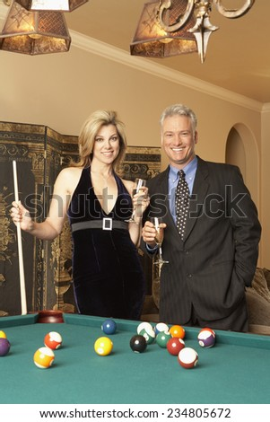 Wealthy Couple at Pool Table - stock photo