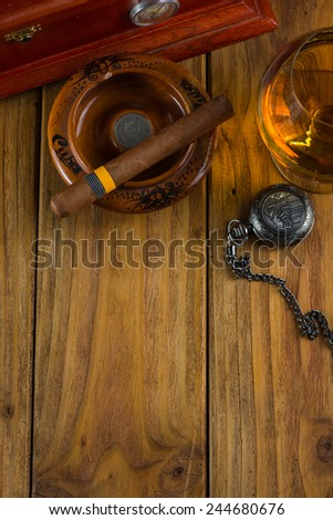 Wealthy man desk, cuban cigars dollar notes, vintage watch and alcohol - stock photo