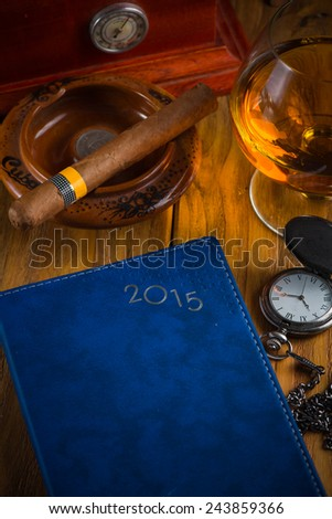 wealthy man desk with cigars, vintage watch cognac and year planner - stock photo