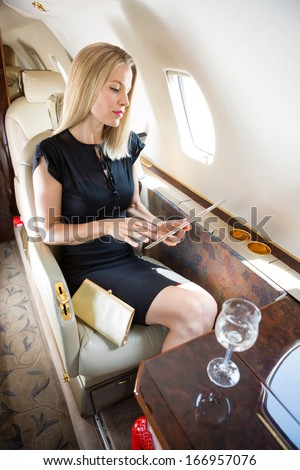 Wealthy mid adult woman using tablet computer in private jet - stock photo
