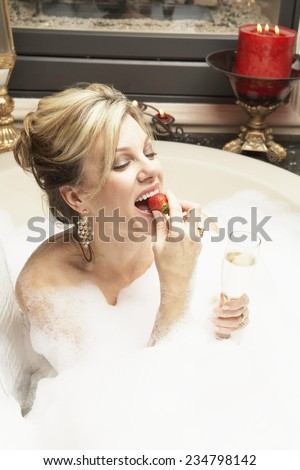 Wealthy Woman Eating Strawberry in Bubble Bath - stock photo