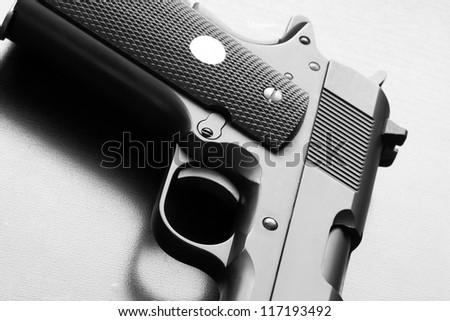 Weapon legends. Black and white picture of 1911 series army pistol on a wooden surface close-up. Studio shot. - stock photo