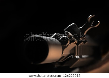 Weapon series. Front view of AR-15 carbine against a black background. Close-up of a cas block and front sight. - stock photo