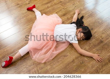 Wear shoes little girl sleeping on the wooden floor