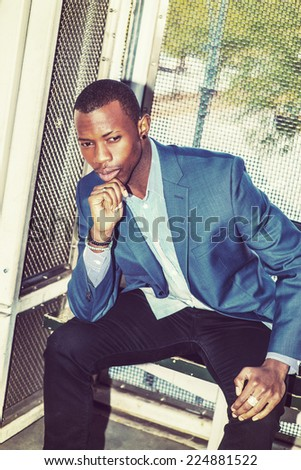 Wearing a blue blazer, black pants,, short haircut, ear stud,  bracelets, finger ring, a young black business man is sitting on bench outside, a hand touching his chin, bending over, thinking. - stock photo