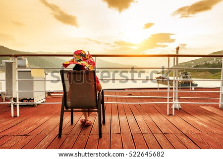 Wearing a large hat along the woman, on the deck of the cruise ship to see the sunrise