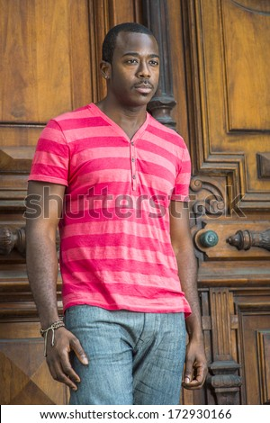 Wearing a red, pink stripe Henley V Neck shirt, gray pants, a bracelet, a young handsome black guy with a little mustache is standing by a old fashion style door, lost in thought. / Young Black Guy - stock photo