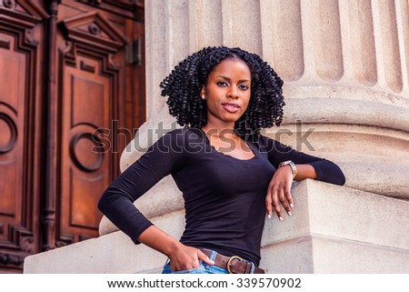 Wearing black long sleeves, V neck top, a young pretty black college student with braid hairstyle standing by column in vintage office building on campus in New York. Filtered look with purple tint.