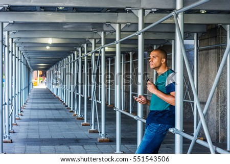 Wearing patterned T shirt, jeans, holding sunglasses, Mixed Race French guy with shaved head sits against metal poles of sidewalk bridge on street in New York, texting, thinking. Color filtered effect