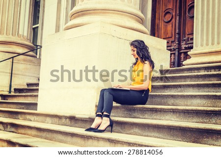 Wearing sleeveless orange shirt, striped pants, high heels, a young East Indian American college student sitting on stairs outside office building on campus, working on laptop computer, reading. - stock photo