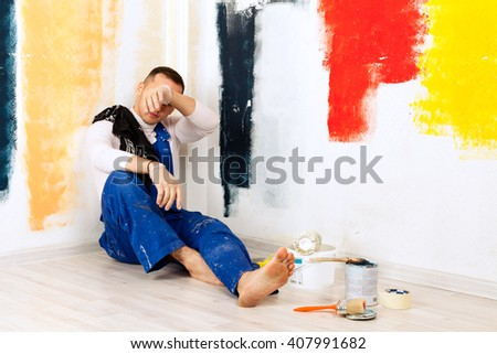 Weary and tired from work painter man sitting on the floor stretching legs, leaning on a colorful wall and wiping his forehead - stock photo