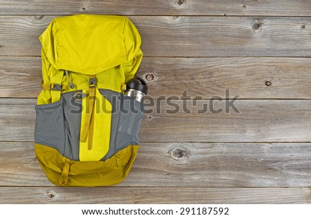 Weather proof backpack with metal canteen on rustic wooden boards.  - stock photo