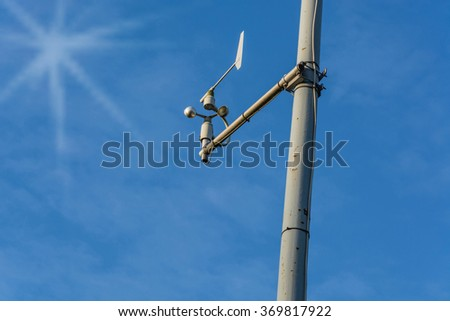 Weather station with anemometer on blue sky. - stock photo
