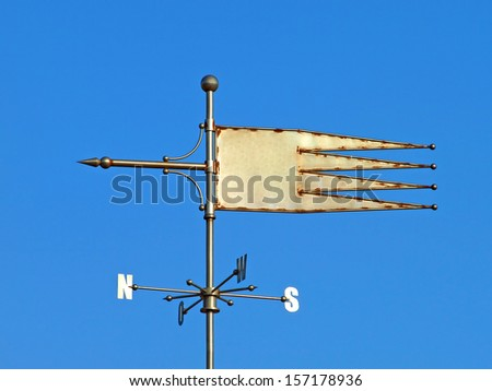 Weather vane against blue sky. - stock photo