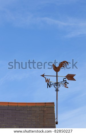 Weather vane - cockerel on a roof, set against a blue sky. - stock photo