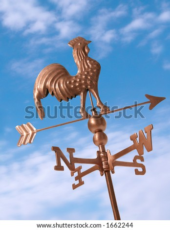 Weather vane in the blue sky - stock photo
