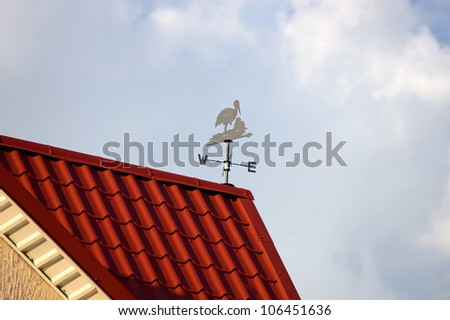 Weather vane on the roof against a sky - stock photo