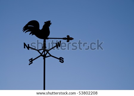 Weather vane silhouetted against a clear blue sky - stock photo