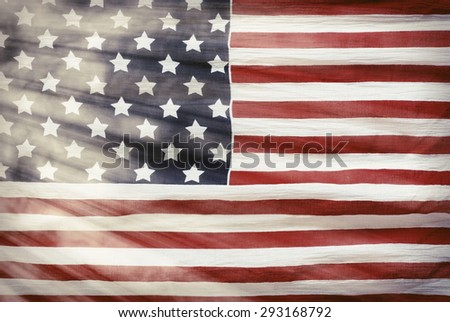 weathered American flag with sun flares background - stock photo
