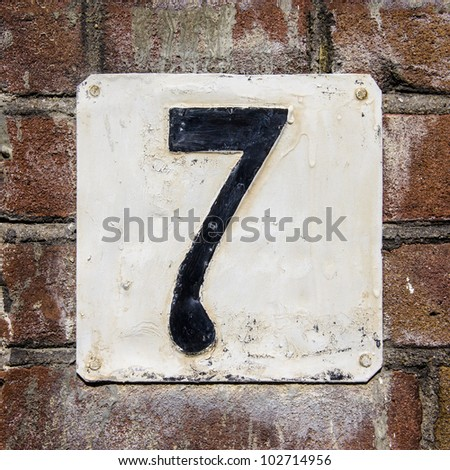 weathered and crackled house number seven on a brick wall - stock photo