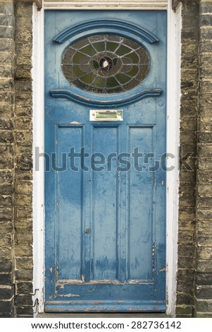 Weathered blue wooden door with stained glass details - stock photo