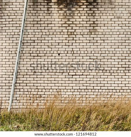 weathered brick wall background metal ladder - stock photo
