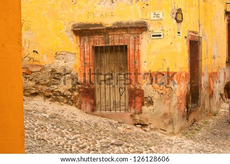 Weathered building facade on a hillside street in old Mexico