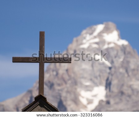 weathered cross with mountain backdrop - stock photo