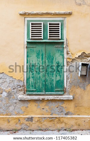 Weathered green window shutters with peeling paint and cracking plaster. Attached to the ancient weathered wall is an electricity meter. - stock photo