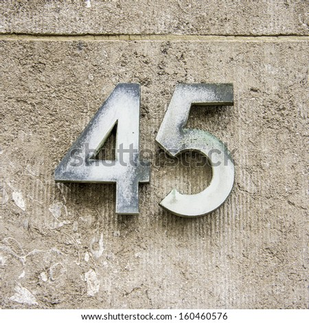 weathered house number forty five. Two separate numerals - stock photo