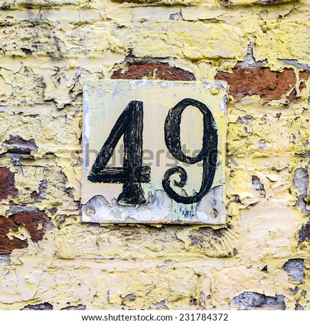 weathered house number forty nine on a wall with flaking paint - stock photo