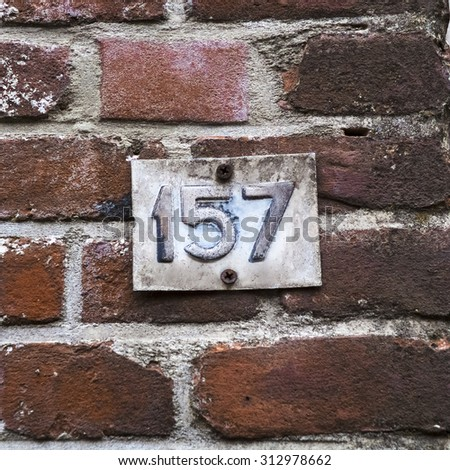 Weathered house number one hundred and fifty seven, embossed in a metal palte. - stock photo