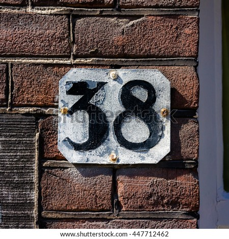 Weathered house number thirty eight - stock photo