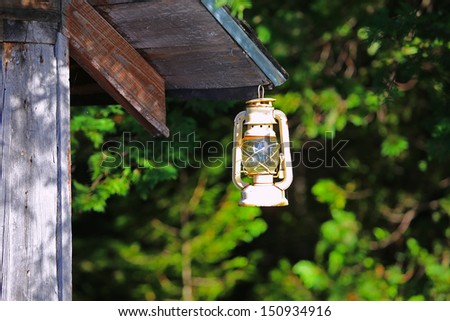 Weathered kerosene lantern hanging from eave of rough hewn wood cabin with green foliage out of focus in the background
