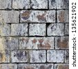 Weathered old railway bridge brick wall background texture with vibrant moss, lichen, cracks, heavy erosion & disintegration - stock photo