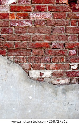 Weathered red brick wall half covered with cement - stock photo