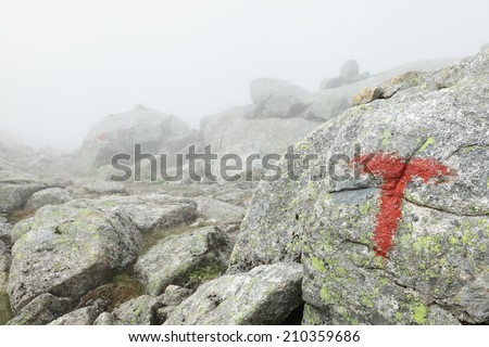 Weathered red marking of hiking track at Syv Sostre mountains at Helgeland coast, Norway. One has to be careful with fog, not to loose sight of the track in thick fog.  - stock photo