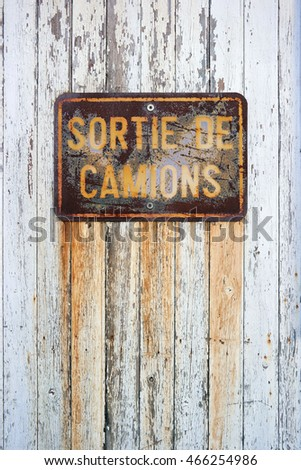 Weathered Sign: Sortie de Camions - Trucks output. Rusty sign in French with: truck exit, on a white painted wooden panel