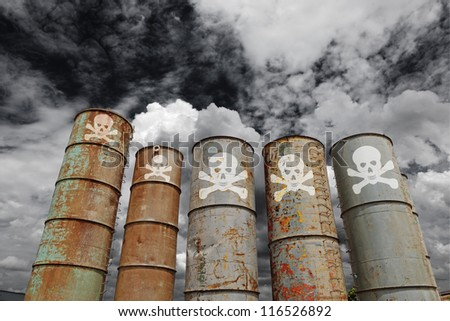 Weathered steel toxic storage silo with skull and crossbones symbol rising up against a dramatic apocalyptic sky for the concept of environmental destruction. - stock photo