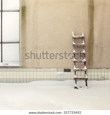 weathered stucco wall with wooden ladder background, old swiming pool - stock photo