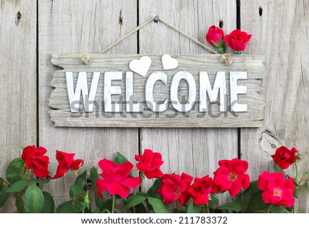 Weathered welcome sign with hearts hanging on wood fence with flower border of red roses - stock photo