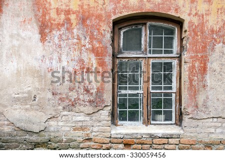 Weathered window with metal safety bars and old shabby building wall