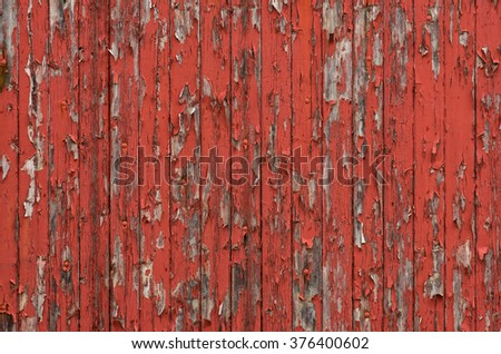 Weathered wooden boards with peeling red paint - stock photo