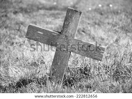 Weathered wooden cross marking a grave - monochrome processing - stock photo