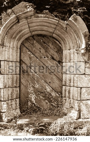 Weathered wooden door with rusty decorative key hole. Old farmhouse in Brittany, France. Aged photo. Sepia. - stock photo