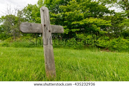 Weathered wooden grave cross sticking up from grass. The cross is blank, there is no text. Trees are in the background. There is room for text on the right. - stock photo