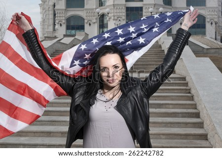 Weaving US flag in hands of patriotic latino women outdoors - stock photo