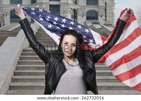 Weaving US flag in hands of patriotic latino women outdoors/ She is looking at camera and smiling - stock photo