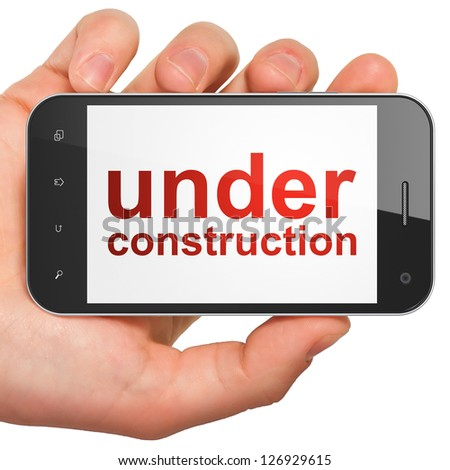 Web design SEO concept: hand holding smartphone with word Under Construction on display. Generic mobile smart phone White background.