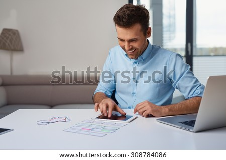 Web designer planning responsive design on digital tablet - stock photo